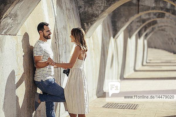 Spanien  Andalusien  Malaga  glückliches  liebevolles Touristenpaar unter einem Torbogen in der Stadt