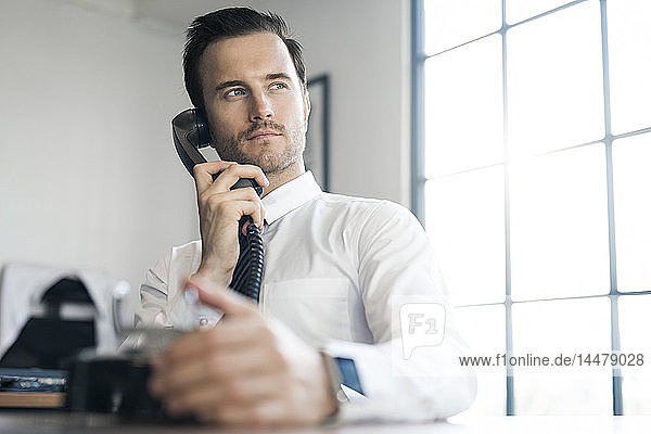 Businessman in office using vintage retro telephone
