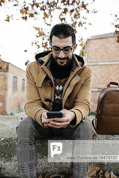Spanien  Igualada  lächelnder sitzender Mann mit Handy in der Herbststadt