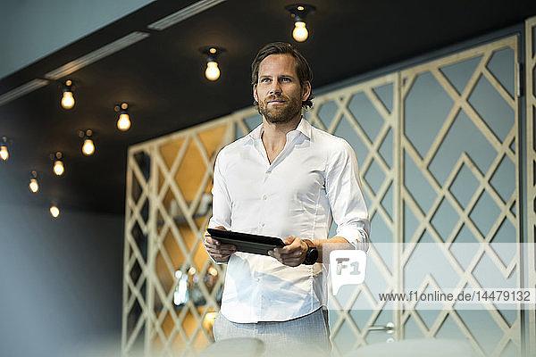 Zuversichtlicher Unternehmer steht in Büro-Lounge und hält Tablett