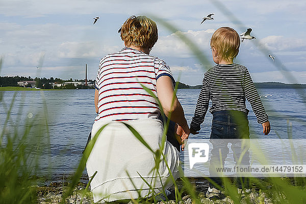 Finnland  Kuopio  Rückenansicht von Mutter und kleiner Tochter beim Beobachten von Möwen am Seeufer