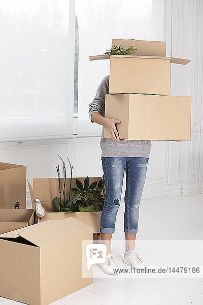 Nicht erkennbare Frau mit Pappkartons in neuem Zuhause