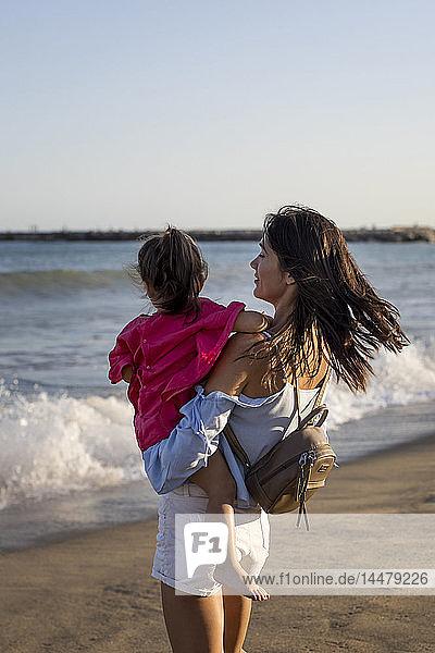 Mutter und Tochter stehen bei Sonnenuntergang am Strand