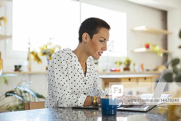 Frau benutzt Laptop auf dem Tisch