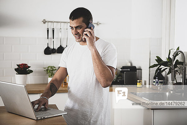 Smiling young man using laptop and cell phone in kitchen at home
