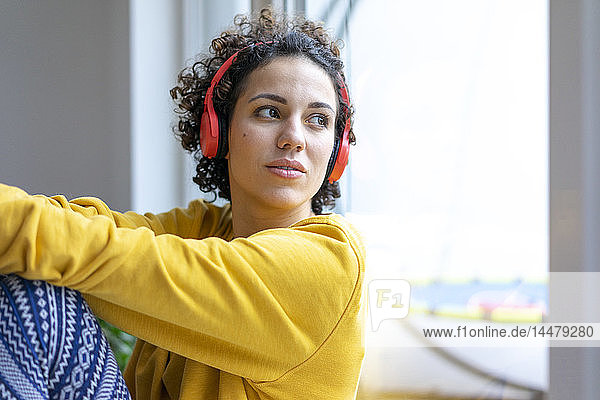 Frau mit Kopfhörern  die aus dem Fenster schaut