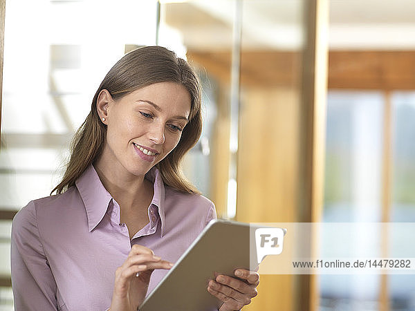 Lächelnde Geschäftsfrau benutzt Tablett im Büro