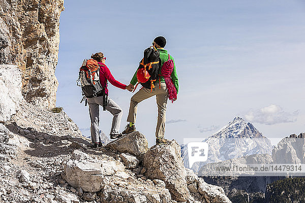 Italien  Cortina d'Ampezzo  Paar mit Seil und Kletterausrüstung hält sich an den Händen und schaut auf die Aussicht