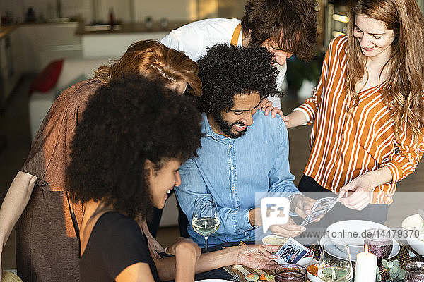 Friends sitting at dining table,  looking at photographs