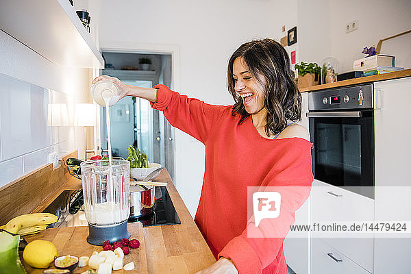 Woman prearing fruit smoothie in her kitchen