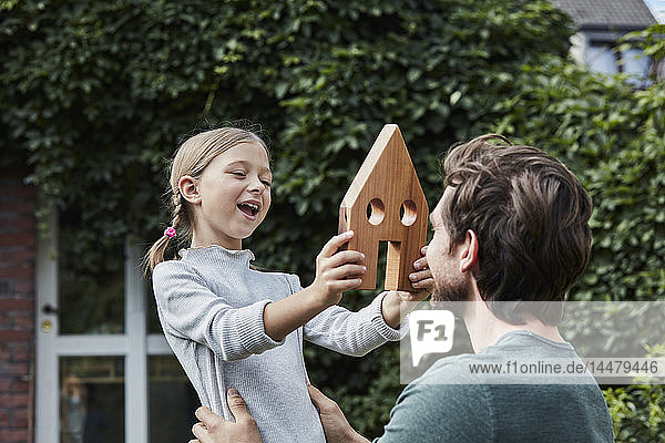 Father and daughter in garden of their home with house model
