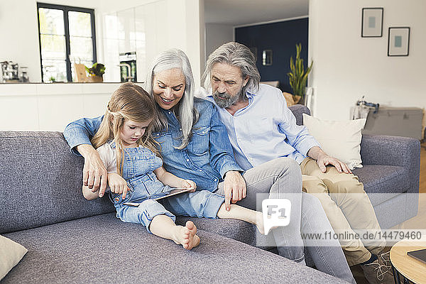 Grandparents and granddaughter sitting on couch  using tablet