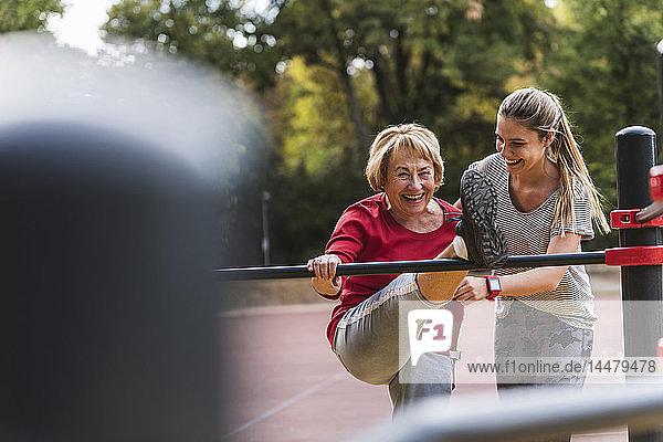 Großmutter und Enkelin trainieren an Bars in einem Park