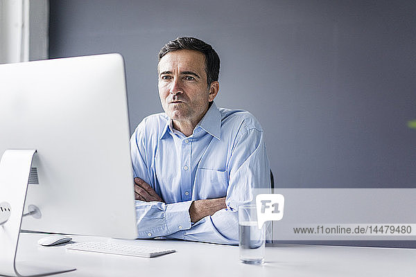Seriöser Geschäftsmann  der im Büro am Schreibtisch sitzt und auf den Computerbildschirm schaut