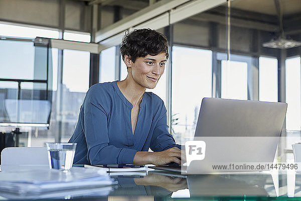 Businesswoman sitting at desk in office using laptop