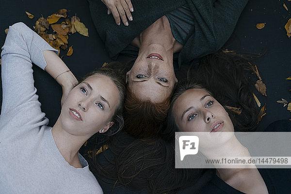 Mutter mit zwei Mädchen im Teenageralter im Herbst auf dem Trampolin liegen