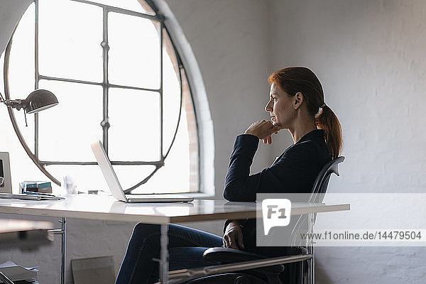 Geschäftsfrau mit Laptop am Schreibtisch im Büro sitzend
