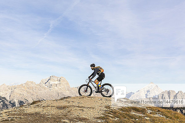 Italy  Cortina d'Ampezzo  man cycling with mountain bike in the Dolomites mountains