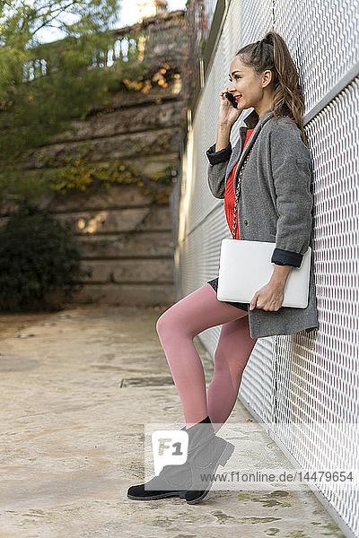 Junge Frau lehnt an einer Wand  telefoniert  hält Digitaö-Tablett