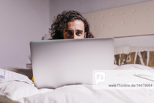 Portrait of young man in bed at home using laptop