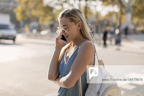 Junge Frau telefoniert in der Stadt mit dem Handy