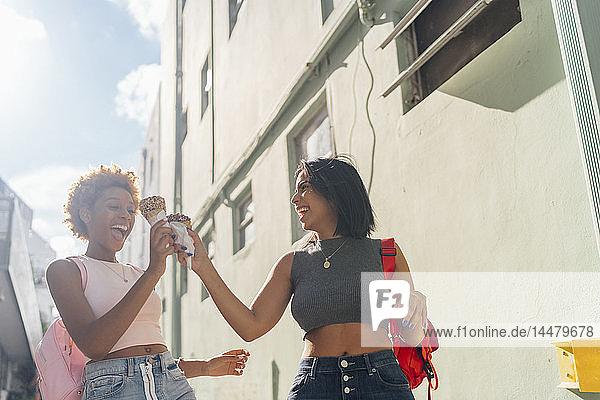 USA  Florida  Miami Beach  two happy female friends with ice cream cones in the city