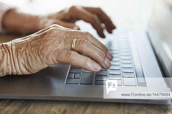 Hand einer älteren Frau beim Tippen auf der Tastatur eines Laptops  Nahaufnahme