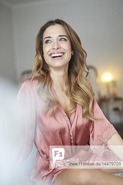 Glückliche junge Frau im Morgenmantel auf dem Bett sitzend