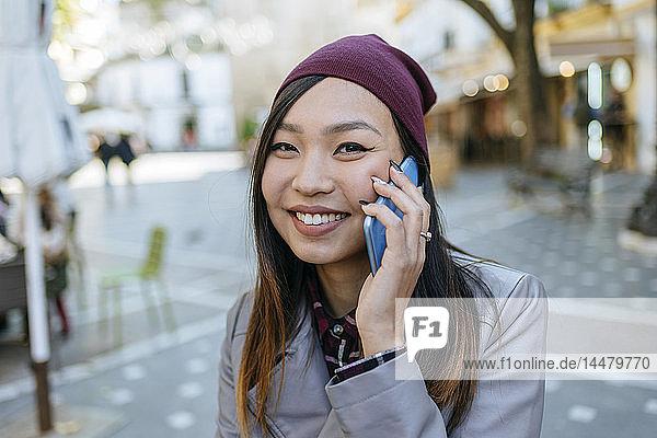 Porträt einer lächelnden jungen Frau am Telefon