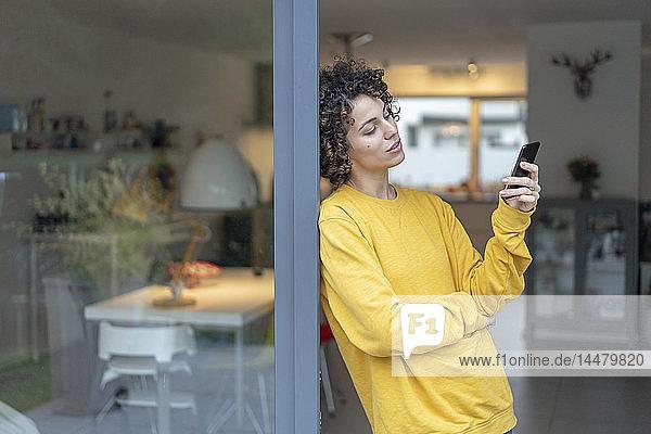 Frau lehnt zu Hause an Terrassentür und überprüft Handy