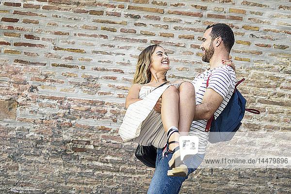 Glücklicher Mann mit Rucksack trägt Freundin an Ziegelmauer