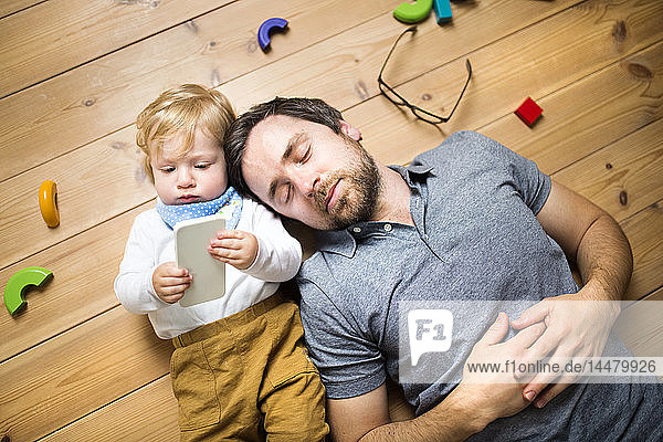 Father lying on floor with his little son playing with smartphone