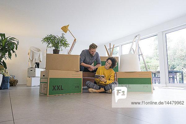 Im Wohnzimmer sitzendes Paar mit Pappkartons und Tablette