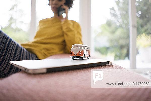 Wohnmobilmodell auf Laptop mit Frau im Hintergrund
