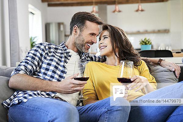 Glückliches Paar sitzt im Wohnzimmer und trinkt Rotwein