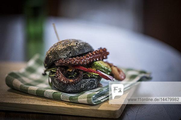Schwarzer Burger mit gebratenem Tintenfisch und Gemüse