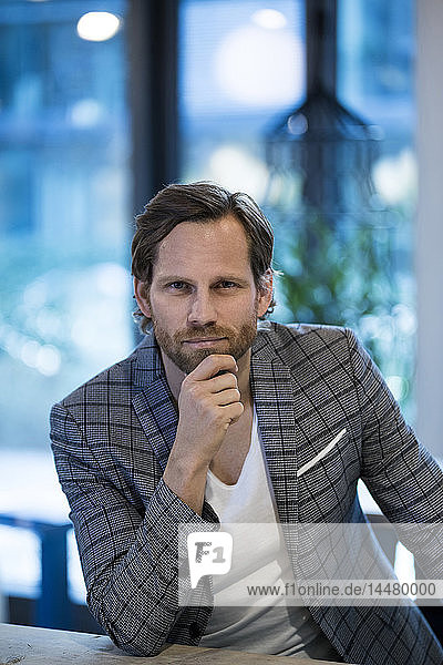 Portrait of confident smart entrepreneur in modern office lounge