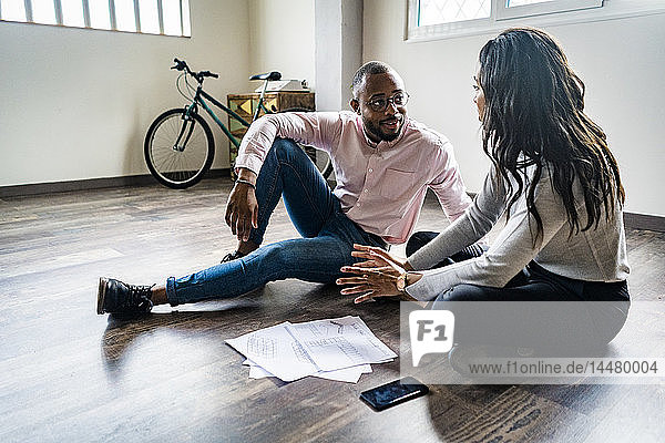 Businessman and businesswoman sitting on the floor discussing documents