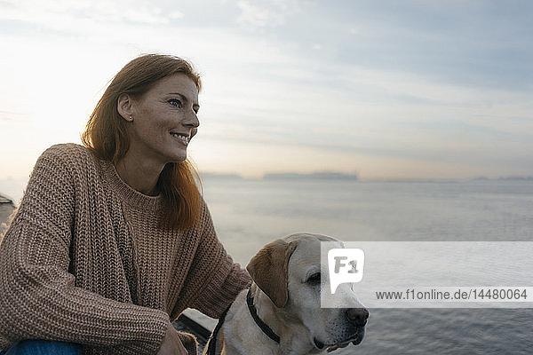 Deutschland  Hamburg  lächelnde Frau mit Hund am Elbufer