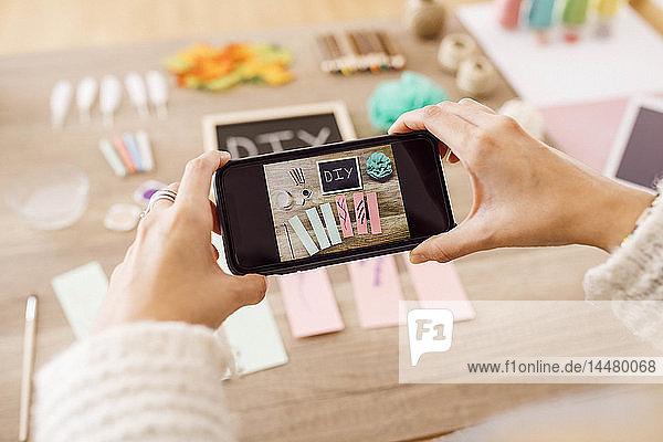 Draufsicht einer jungen Frau  die mit einem Smartphone Fotos für ihren Bastel-Blog macht