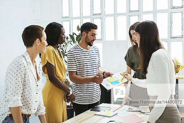 Kollegen arbeiten zusammen am Schreibtisch im Büro und diskutieren Papiere
