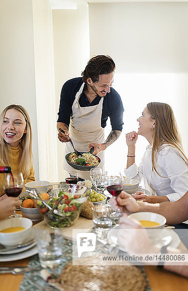 Freunde essen zusammen zu Mittag  Gastgeber serviert Pasta
