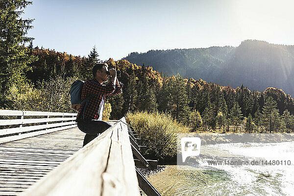 Österreich  Alpen  Mann auf Wanderung  der durch ein Fernglas schaut