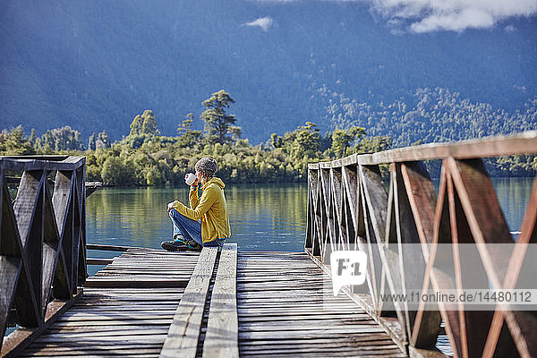 Chile  Chaiten  Lago Rosselot  woman sitting on jetty drinking from mug