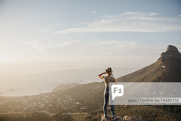 South Africa  Cape Town  Kloof Nek  woman standing on rock at sunset