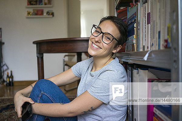 Happy young woman sitting at home  leaning on book shelf