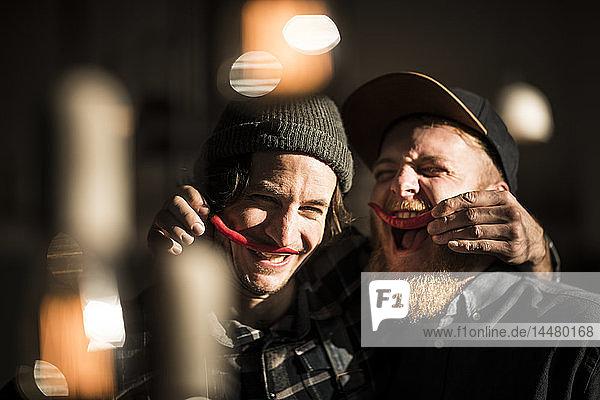 Freunde spielen mit Chilischoten und machen Schnurrbärte