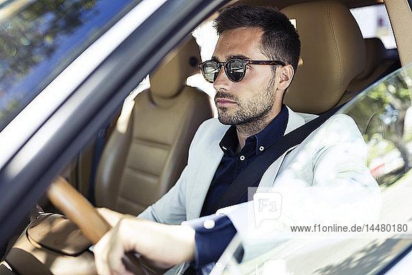 Erfolgreicher junger Geschäftsmann fährt in seinem Auto