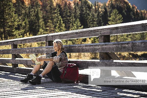 Österreich  Alpen  Frau auf einer Wanderung  die auf einer Brücke sitzt und eine Karte liest