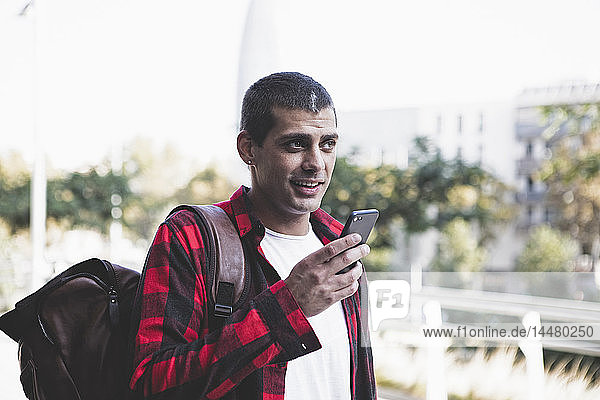 Young man with backpack and cell phone on the go